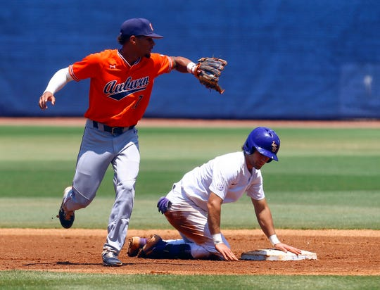 LSU's Josh Smith (4) beats the throw to Auburn shortstop Will Holland (17) as he slides into second during the first inning of an NCAA college baseball game at the Southeastern Conference tournament Thursday, May 23, 2019, in Hoover, Ala. (AP Photo/Butch Dill)