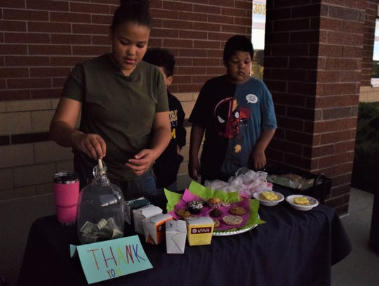 Maya Lee, left ,a fifth-grader at Gorsuch West Elementary, is president of the Cupcake Warriors Club. The club is raising money to help pay off students' school lunch debts. She helped with the bake sale, along with Matthew Hoang, center, and her brother Zachary, right.