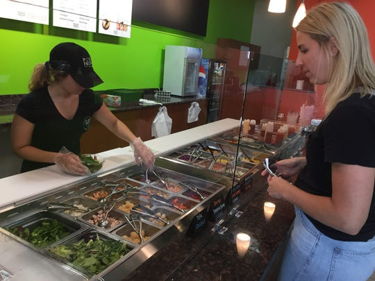 Carly Anderson orders a Hawaiian cuisine-inspired poké bowl at restaurant Poké Fresh's new location in Brighton on opening day, Thursday, May 23, 2019. Employee Elisa Meo assembles the custom-ordered meal.