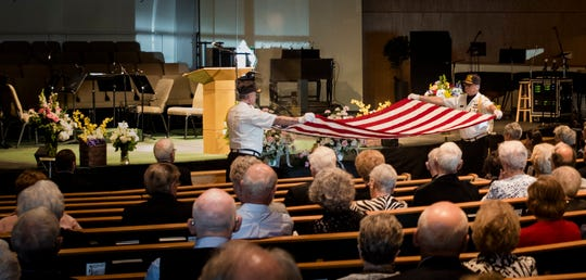 VFW Post 701 Honor Guard members Don Caswell, left, and Mike Spitzley silently fold a U.S. flag Saturday, May 18, 2019, during former U.S. Marine Dale Hansen's funeral at South Church in Lansing.  Ceremonial flag folding requires 13 folds, which represent the original colonies.  The flag is presented to next-of-kin in a triangular shape that represents the three-cornered hats worn by soldiers during the Revolutionary War.