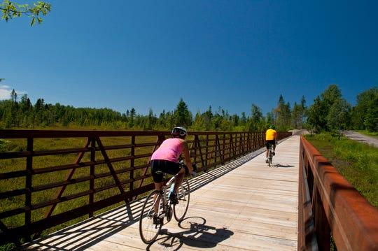 Cyclists ride over a bridge on the Heart of Vilas trail system in Vilas County.