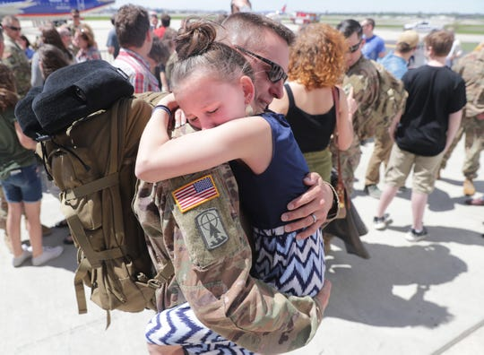 Capitan Michael Lindow hugs his 10-year-old daughter, Amalia, after arriving at the 128th Air Refueling Wing in Milwaukee on Thursday. Lindow's wife, Erin, was there to greet him, too.