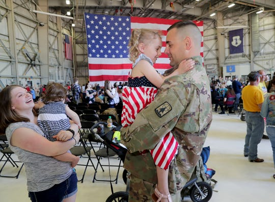 Staff Sgt. Dan Craft of Marshfield greets his 3-year-old daughter, Sydney, as his wife, Sam, and 8-month-old daughter, Lyndsey, look on after he arrived at the 128th Air Refueling Wing on Thursday.