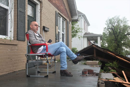 Andrew Buchanan sits on his porch after storms destroyed his roof and collapsed his porch.