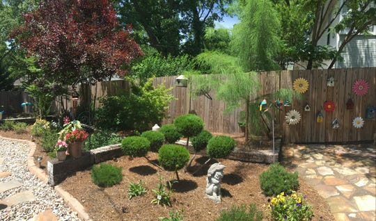 The backyard garden of Herb and Janine McLaughlin features whimsical artwork, herbs, ornamental shrubs and a stone walkway.