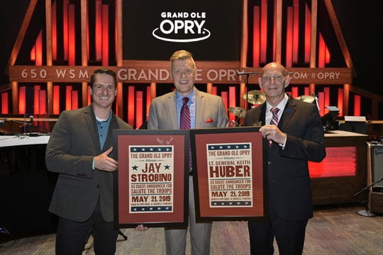 MTSU alumnus and combat veteran Jay Strobino, left, and retired Army Lt. Gen. Keith Huber, the university's senior adviser for veterans and leadership initiatives, right, are congratulated by Grand Ole Opry announcer Bill Cody after the men served as guest announcers for the Opry's Salute The Troops show Tuesday in Nashville, Tenn.