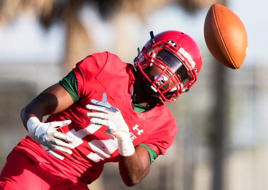 Immokalee High School's Charles Toombs tracks a pass before taking on Clearwater Superior-Collegiate in a spring game at Immokalee on Wednesday. Immokalee beat Clearwater Superior-Collegiate 21-14.