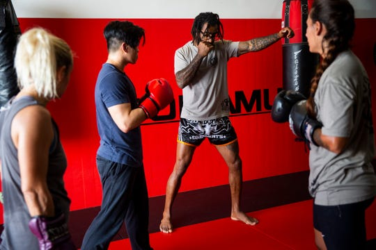 "Cosmo Alexandre, center, coaches students Stephanie Gordon, from left,  Jeremiah ""G"" Salvador and Larissa Freitas during a class at Evolution MMA in North Naples on Wednesday, May 22, 2019. Alexandre beat former UFC fighter Sage Northcutt in a mixed martial arts fight on Friday, May 17, in Singapore."