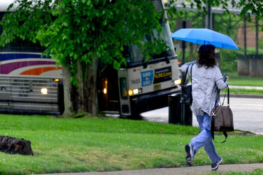 A woman runs to catch an NJ Transit bus on Teaneck Rd on Thursday May 23, 2019 in Teaneck, N.J.