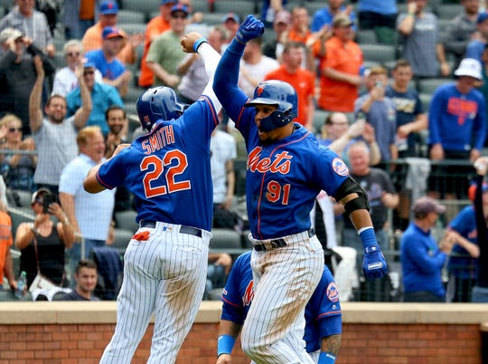 New York Mets right fielder Carlos Gomez (91) is congratulated by New York Mets pinch hitter Dominic Smith (22) after hitting a three run home run against the Washington Nationals during the eighth inning at Citi Field.