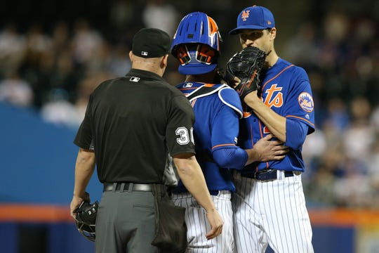 May 22, 2019; New York City, NY, USA; New York Mets catcher Tomas Nido (3) gets between New York Mets starting pitcher Jacob deGrom (48) and home plate umpire Ryan Blakney (36) during the sixth inning against the Washington Nationals at Citi Field.