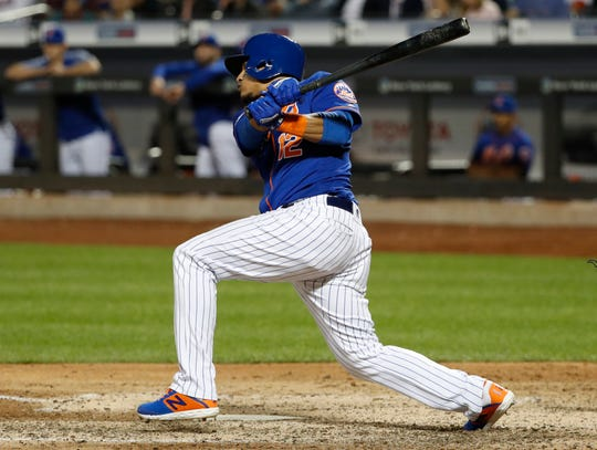New York Mets Juan Lagares watches his three-run double in the eighth inning of the team's baseball game against the Washington Nationals, Wednesday, May 22, 2019, in New York. (AP Photo/Kathy Willens)