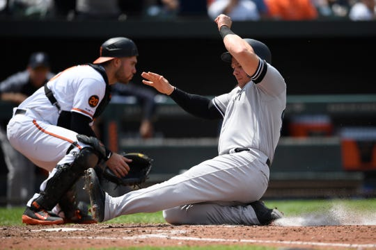 New York Yankees' Luke Voit, front, slides home to score in front of Baltimore Orioles catcher Austin Wynns during the sixth inning of a game, Thursday, May 23, 2019, in Baltimore. The Yankees won 6-5.