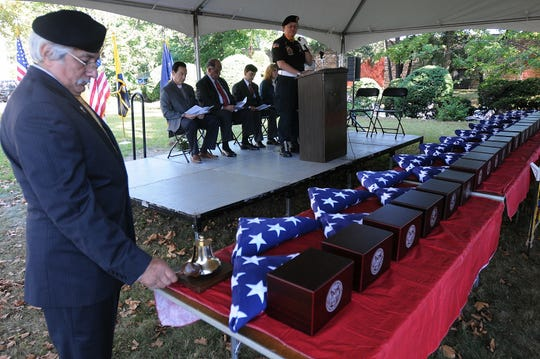 New Jersey's Mission of Honor  chairman Francis Carrasco(L) rings the bell as the names of 25 veterans are called by chaplain Jerry Skorch during a burial service held in 2013 in North Bergen.