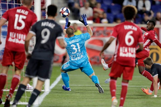 A shot by Vancouver Whitecaps midfielder Scott Sutter, not visible, gets by New York Red Bulls goalkeeper Luis Robles (31) for a goal during the first half of an MLS soccer match Wednesday, May 22, 2019, in Harrison, N.J. (AP Photo/Julio Cortez)