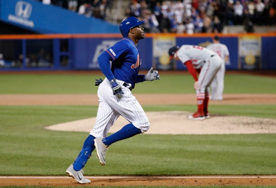 New York Mets' Rajai Davis, left, runs between third and home on his eighth-inning, three-run home run in the team's baseball game against the Washington Nationals, Wednesday, May 22, 2019, in New York, as Nationals relief pitcher Sean Doolittle, right, reacts on the mound.