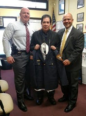 Rev. David Rios, center, in 2015 received his Paterson police chaplain's union and bade from union presidents Mason Maher, left, and Alex Cruz, right.