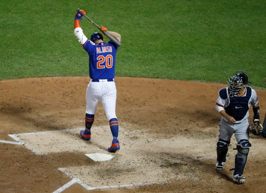New York Mets Pete Alonso (20) reacts after striking out, stranding two runners, during the fifth inning of the team's baseball game against the Washington Nationals on Wednesday, May 22, 2019, in New York. Nationals catcher Kurt Suzuki heads back to the dugout. (AP Photo/Kathy Willens)