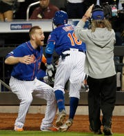 New York Mets'Todd Frazier, left, celebrates with Rajai Davis after Davis hit a three-run home run during the eighth inning of the team's baseball game against the Washington Nationals, Wednesday, May 22, 2019, in New York. (AP Photo/Kathy Willens)