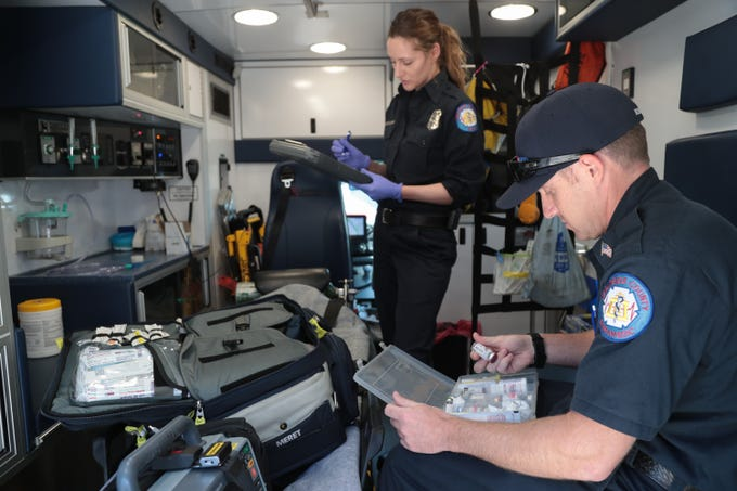 Zach Borba and Kelly Jaeger complete a medical inventory at the start of their shifts at American Medical Response, Palm Springs, Calif., May 22, 2019.