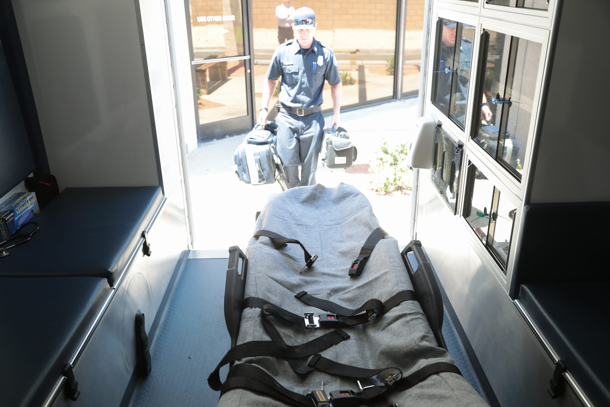 Zach Borba carries equipment into an American Medical Response ambulance at the start of his shift, Palm Springs, Calif., May 22, 2019.