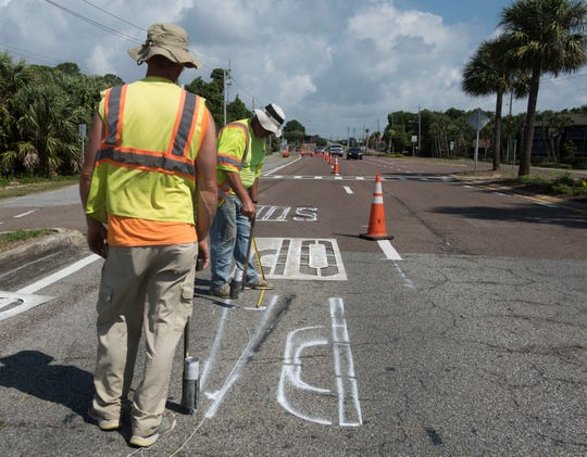 Michael Segers and Jason French with Gulf Coast Traffic Engineering work Thursday to add signageand re-stripelanes heading toward the Bob Sikes Toll Bridge. The changes are part of a plan to add an additional SunPass-only lane and switch the location of the lanes that accept cash and those that use transponders.