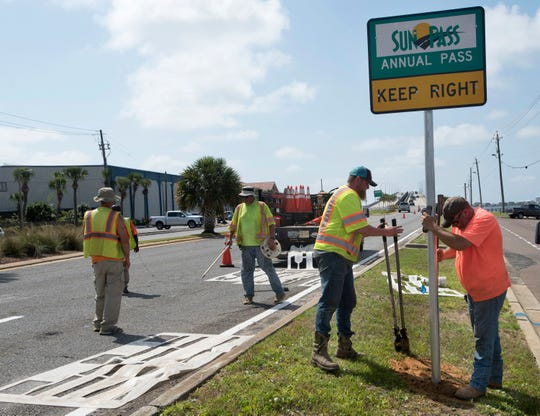 Workers from Gulf Coast Traffic Engineers relocate the sun pass lane just before the Bob Sikes Bridge in Gulf Breeze on Thursday, May 23, 2019. Escambia County officials shifted to the sun pass only toll gates to the two right two lanes at the toll plaza.