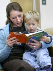 Andrea Keele reads to her son Ethan in the children's area at a Maricopa County library branch.