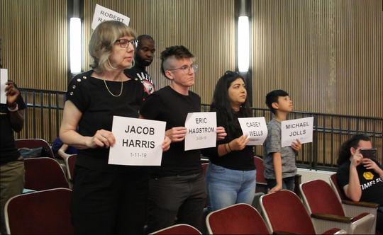 Protesters hold up the names of people killed by Phoenix police this year as Poder in Action Executive Director Viridiana Hernandez speaks to the Phoenix City Council on May 22, 2019.
