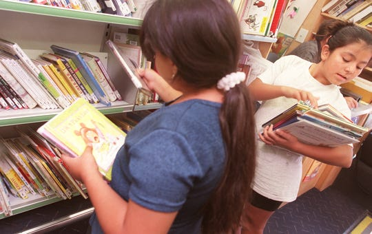 Miriam Perez, 11, right, sorts through a stack of books she selected from a  Maricopa County library while her friend Lorena Villegas picks through the shelves.