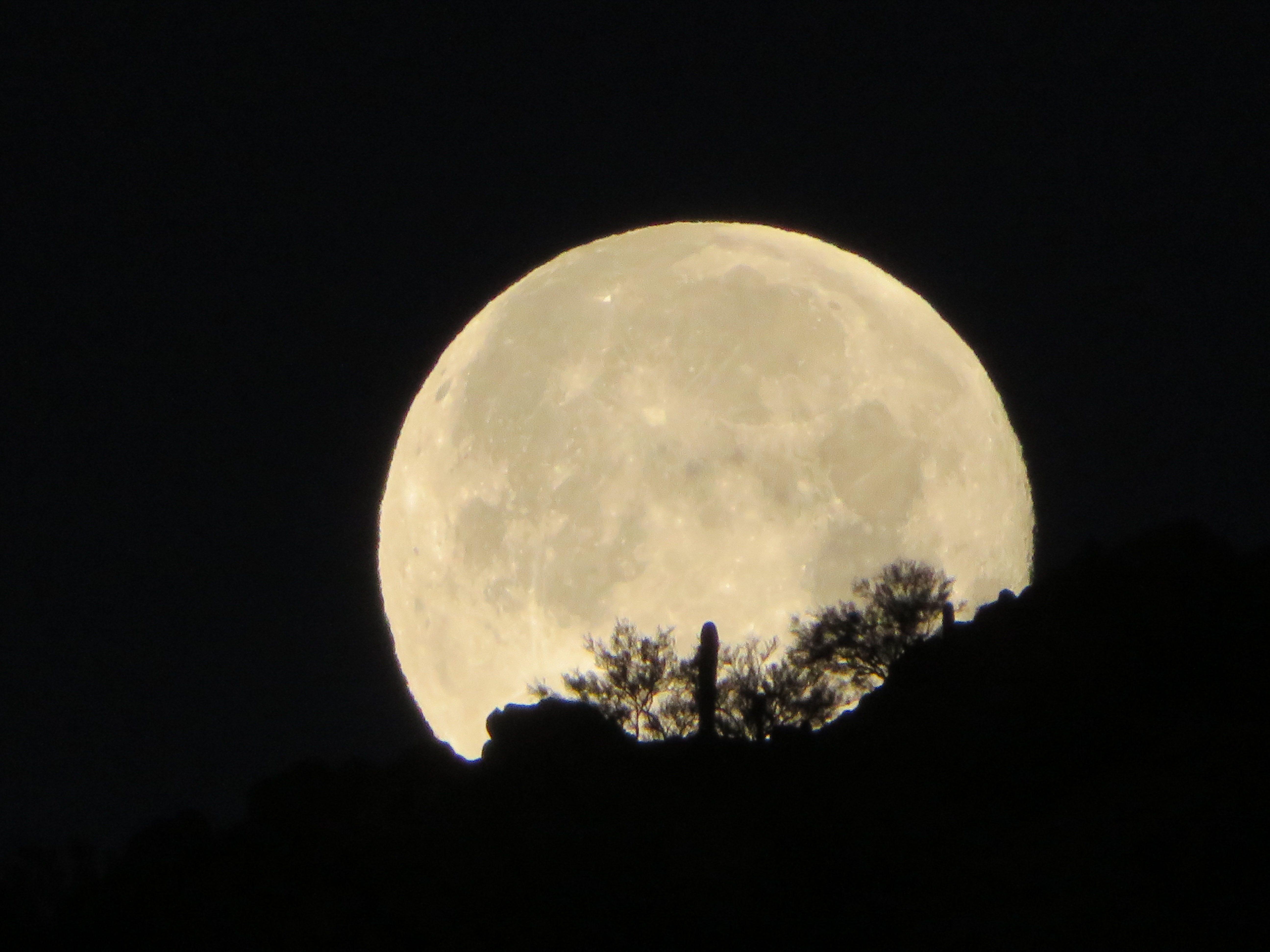 Snow Moon setting behind Camelback Mountain.