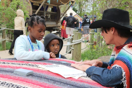 Za'Nyla Becton and Lamar Lewis, of Akron, speak with the Cedar Point's Blackjack, a living character in their new Forbidden Frontier and Adventure Island exhibit.