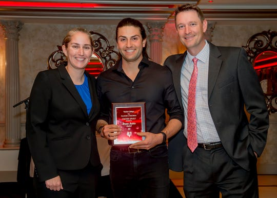 Vassar College baseball player Bryan Rubin (center) is flanked by athletic director Michelle Walsh and coach Matthew Righter as he receives an award at the school's May 8 banquet.