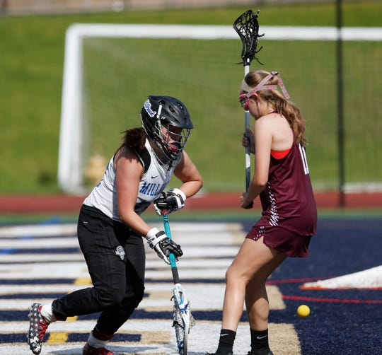 Millbrook goalie Claire Martell, after a save, rolls the ball between an opponent's legs, making a pass to herself, during the Section 9 Class D girls lacrosse final on Wednesday.