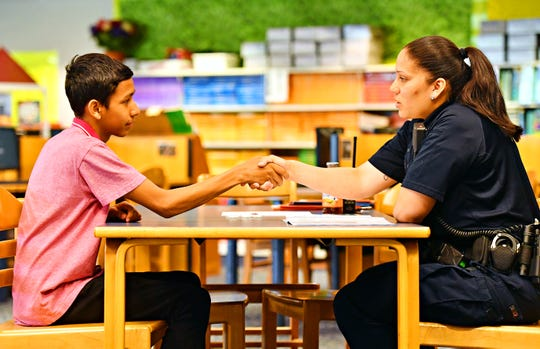 Eighth-grader Ramses Montalvo, and York City School Police Officer Angie Mateo shake hands at the conclusion of a mock job interview at Hannah Penn K-8 School in York City, Thursday, May 23, 2019. The day is a culmination of efforts to train and guide students through the process of preparing a portfolio to market themselves for jobs, as well as coaching them through the interview process. Dawn J. Sagert photo