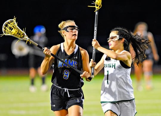 Kennard-Dale's Megan Halczuk, left, moves the ball down the field while York Catholic's Olivia Staples defends during District III, Class 2-A girls' lacrosse championship action at Central Dauphin Middle School in Harrisburg, Wednesday, May 22, 2019. York Catholic would win the game 12-9. Dawn J. Sagert photo