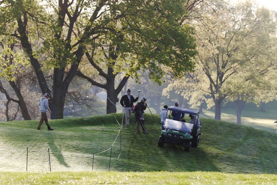 Groundskeepers put the final touches on the Oak Hill course Thursday morning.