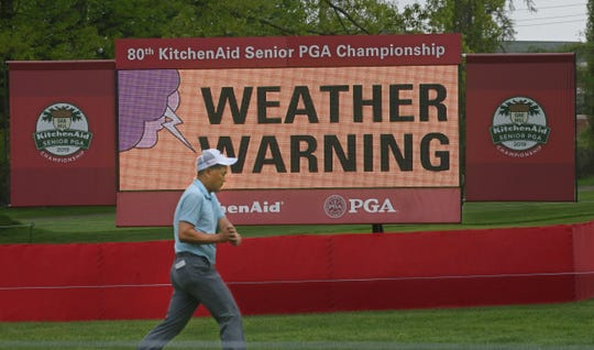 Taichi Teshima walks down the 17th fairway as a weather warning sign flashes during the first round.