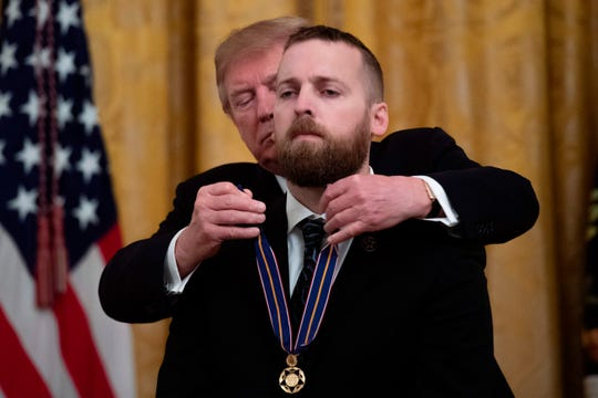 US President Donald Trump (L) awards Oregon State Police Trooper Nicholas  Cederberg the Public Safety Officer Medal of Valor at the White House in Washington, DC on May 22, 2019.