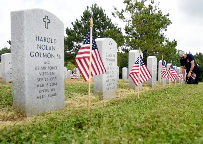 Volunteers place American flags on the gravesites at Northwest Louisiana Veterans Cemetery Thursday, May 23, 2019 in preparation for Memorial Day.