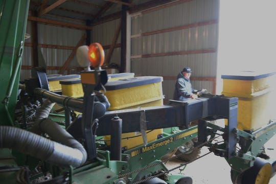 Garretson area farmer Jim Solheim does maintenance work on a planter. Solheim and other farmers have been delayed in planting this year's corn and soybean crops due to wet and cold weather.