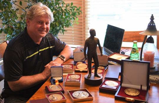 Jurek Jakowicz poses with a few pieces from his collection of medallions.