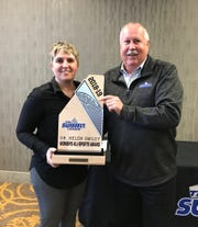 South Dakota associate athletic director for compliance and senior woman administrator Jamie Oyen poses for a photo with Summit League commissioner Tom Dupel and the Dr. Helen Smiley Women's All-Sports Award.