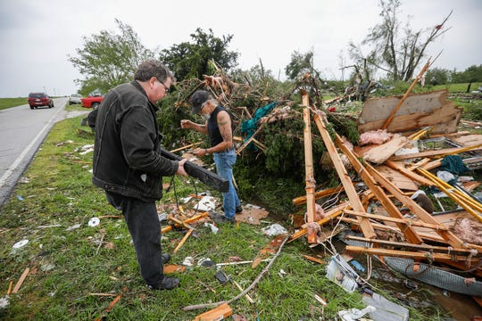 Kenneth Arles, the brother of Mark Berg, left, and Dean Eastin, Betty Berg's friend, look through debris the tornado left in Golden City on May 23, 2019.