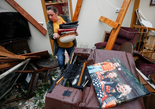 Amanda Walker walks past a portrait of her niece, nephew, and daughter as she carries items out of her home that was severely damaged by a tornado that moved through Carl Junction on Wednesday, May 22, 2019.