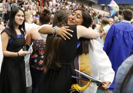 Graduate Amy Cortes hugs friends at the conclusion of the Fort Defiance High School commencement ceremony at Eastern Mennonite University in Harrisonburg on Wednesday, May 22, 2019.