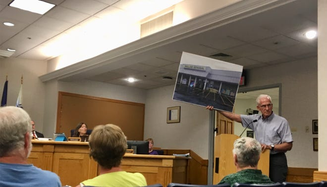 Resident Martin Lightsey held a sign to show what a Dollar General store typically looks like. He was among residents that oppose the store opening on Springhill Road.