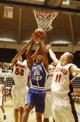 Lee High's Tyler Crawford goes up for a shot against Albemarle's Daniel Johnson and Brett Maynard during a game at University Hall in 2003.