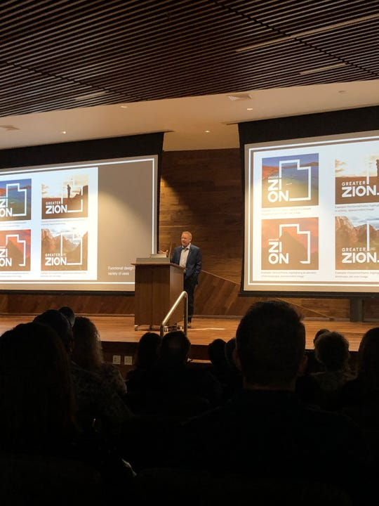 Kevin Lewis, Director of Greater Zion, reveals the different formats of the new logo to the crowd at the brand relaunch event on May 23, 2019.