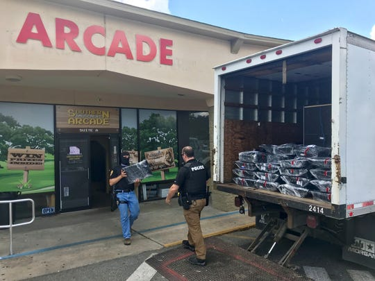 Tallahassee police officers load up confiscated equipment at the Southern Amusement Arcade as part of raids conducted on suspected gambling houses Thursday, May 23, 2019. The raids were part of joint operation of the Tallahassee Police Department and the Leon County Sheriff's Office.